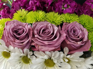 Layers of fresh flowers arranged in horizontal rows of purple stock, green button mums, lavender roses, and white daisies