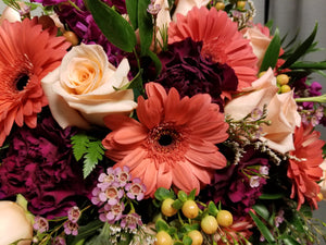 Assorted fresh flowers in shades of pink, coral, purple, and lavender with greenery