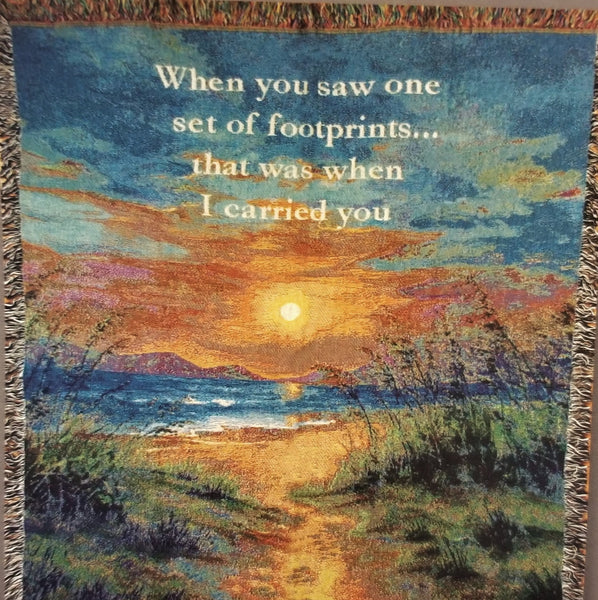"Close up view. Woven throw features a beautiful beach sunset scene and the verse ""When you saw one set of footprints...that was when I carried you."""