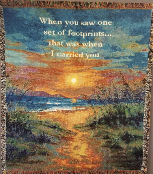 "Full view. Woven throw features a beautiful beach sunset scene and the verse ""When you saw one set of footprints...that was when I carried you."""