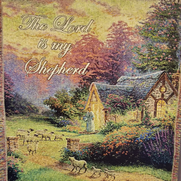 "Close up view. Woven throw features a Thomas Kinkade image of a small cottage in the woods surround by blooming gardens with a man calling a flock of sheep to him. Afghan reads, ""The Lord is my Shepherd"""