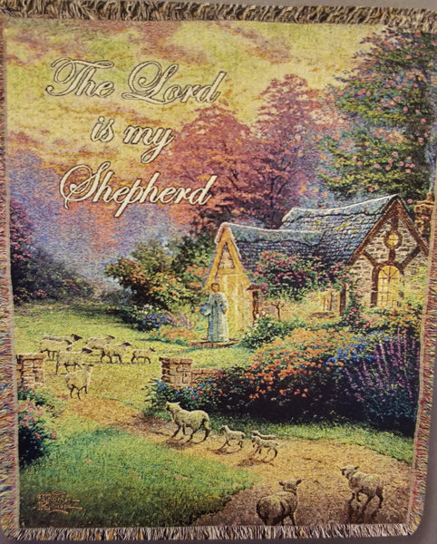 "Full view. Woven throw features a Thomas Kinkade image of a small cottage in the woods surround by blooming gardens with a man calling a flock of sheep to him. Afghan reads, ""The Lord is my Shepherd"""