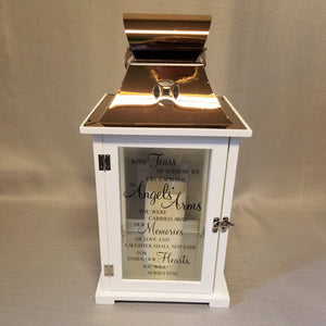 "White wooden lantern with bronze metal top and built-in candle. Verse reads, ""With tears of sorrow we cry each day, in angels' arms you were carried away. Our memories of love and laughter shall not fade, for inside our hearts you will always stay."""