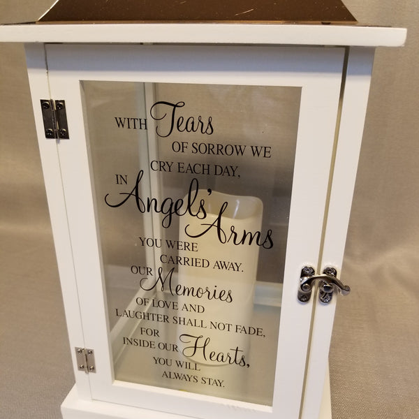 "Close up view. White wooden lantern with bronze metal top and built-in candle. Verse reads, ""With tears of sorrow we cry each day, in angels' arms you were carried away. Our memories of love and laughter shall not fade, for inside our hearts you will always stay."""