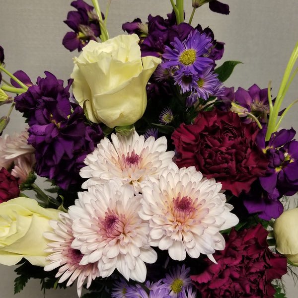 Close up view of white roses, lavender mums, purple carnations, purple stock, and lavender filler flowers