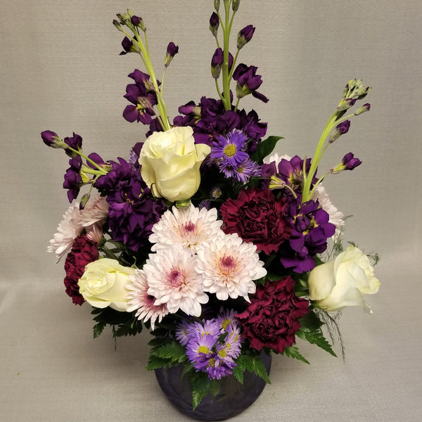 Lavender glass vase filled with assorted purple and lavender flowers with white roses.