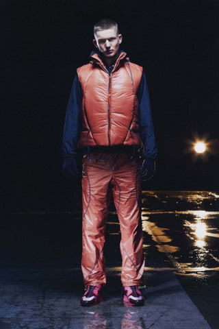 Male model wearing orange puffa gilet and trousers from Saul Nash