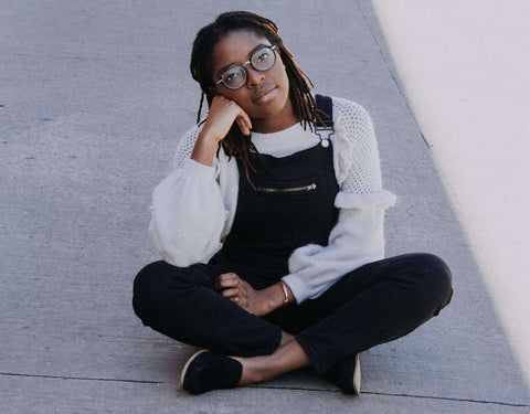 Woman wearing black dungarees and a white vintage sweater posing while sitting down