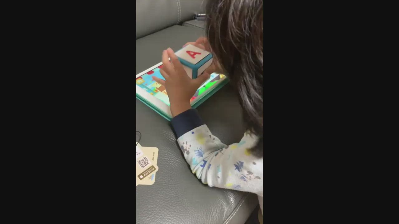 Young girl spelling English with Cookie Kiddle cube