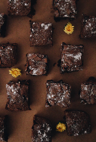 CBD flower-infused brownies covered with powdered sugar and yellow flowers for decoration