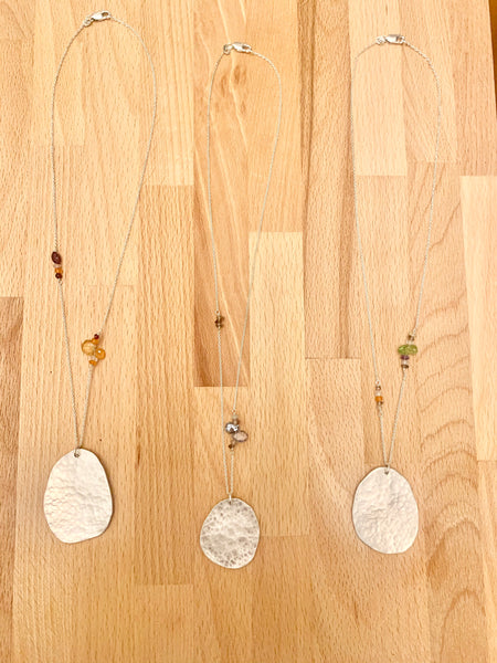 Hammered silver pendant necklaces.