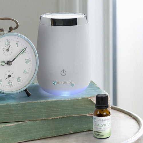 Eucalyptus Essential Oil next to aroma machine in antique-looking bedroom