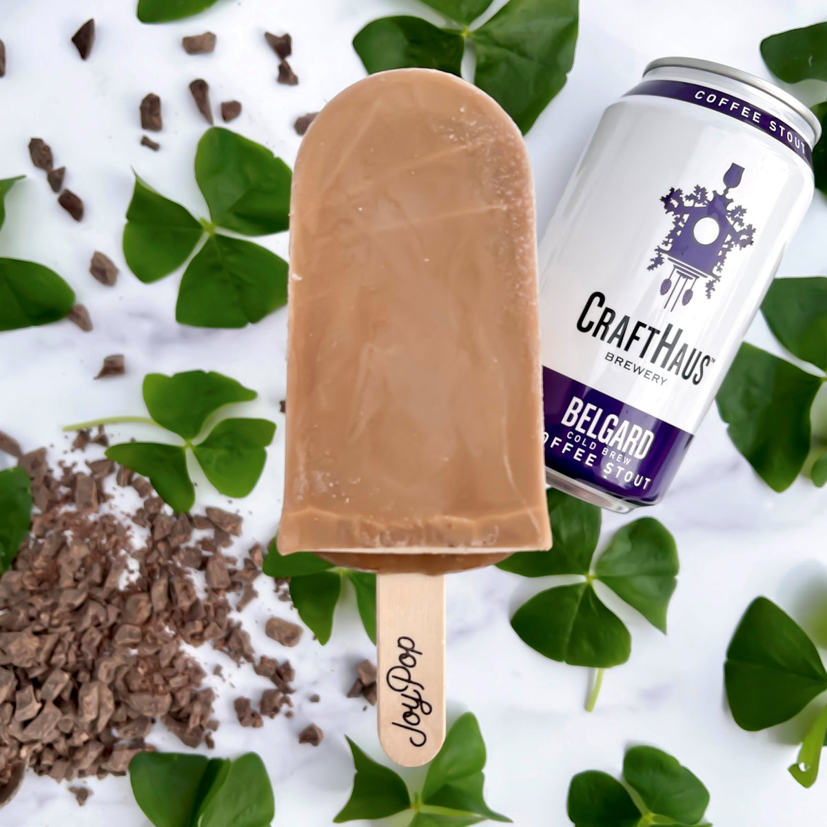 Belgard Chocolate Stout Frozen Pop by The Joy Pop Co with chocolate pieces, clovers and a belgard coffee stout CraftHaus can on a white marble background