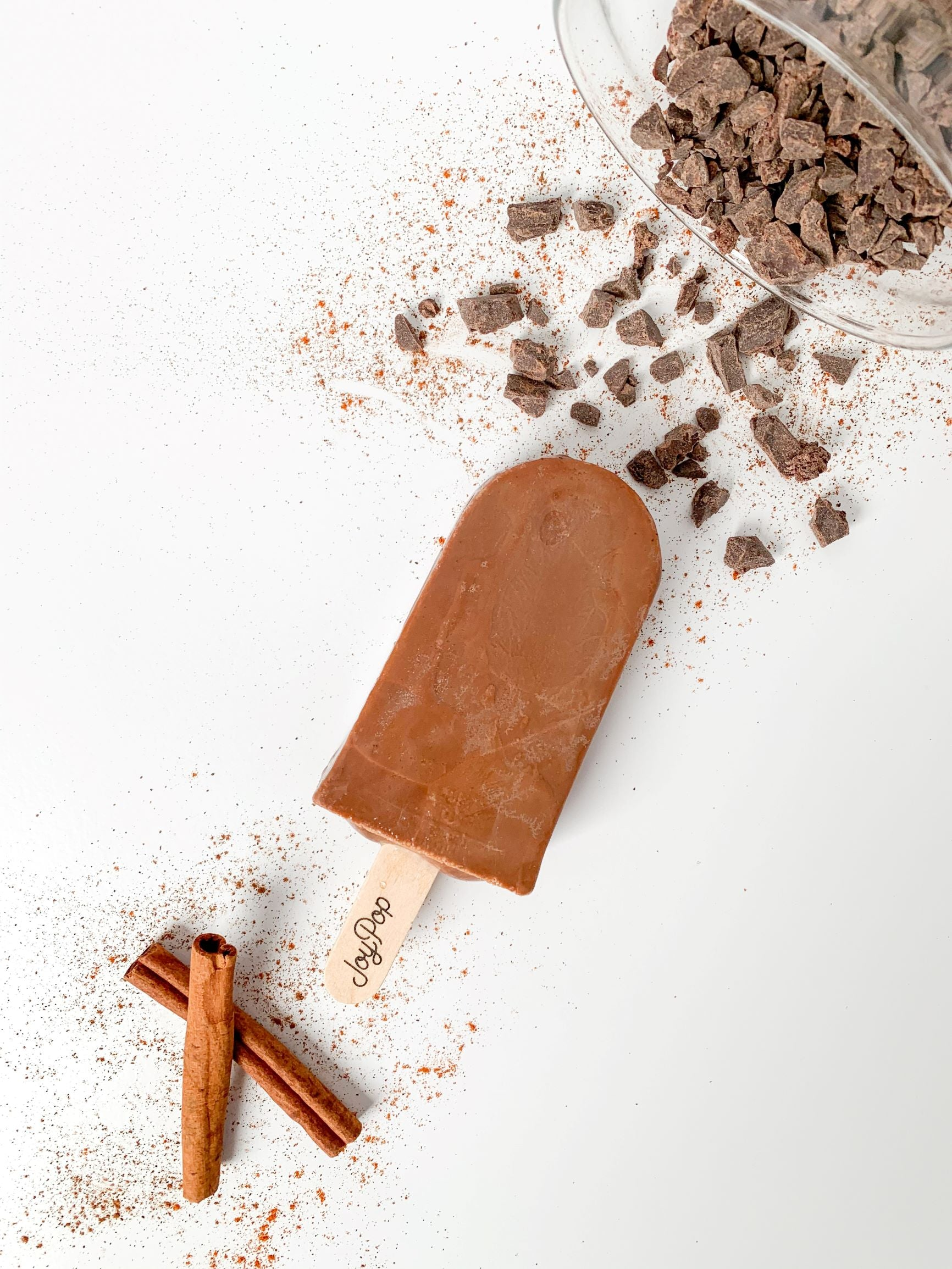 Mexican hot chocolate pop from The Joy Pop Co next to cinnamon sticks and cinnamon spice and a glass jar of chocolate chunks that is spilling out on a white background