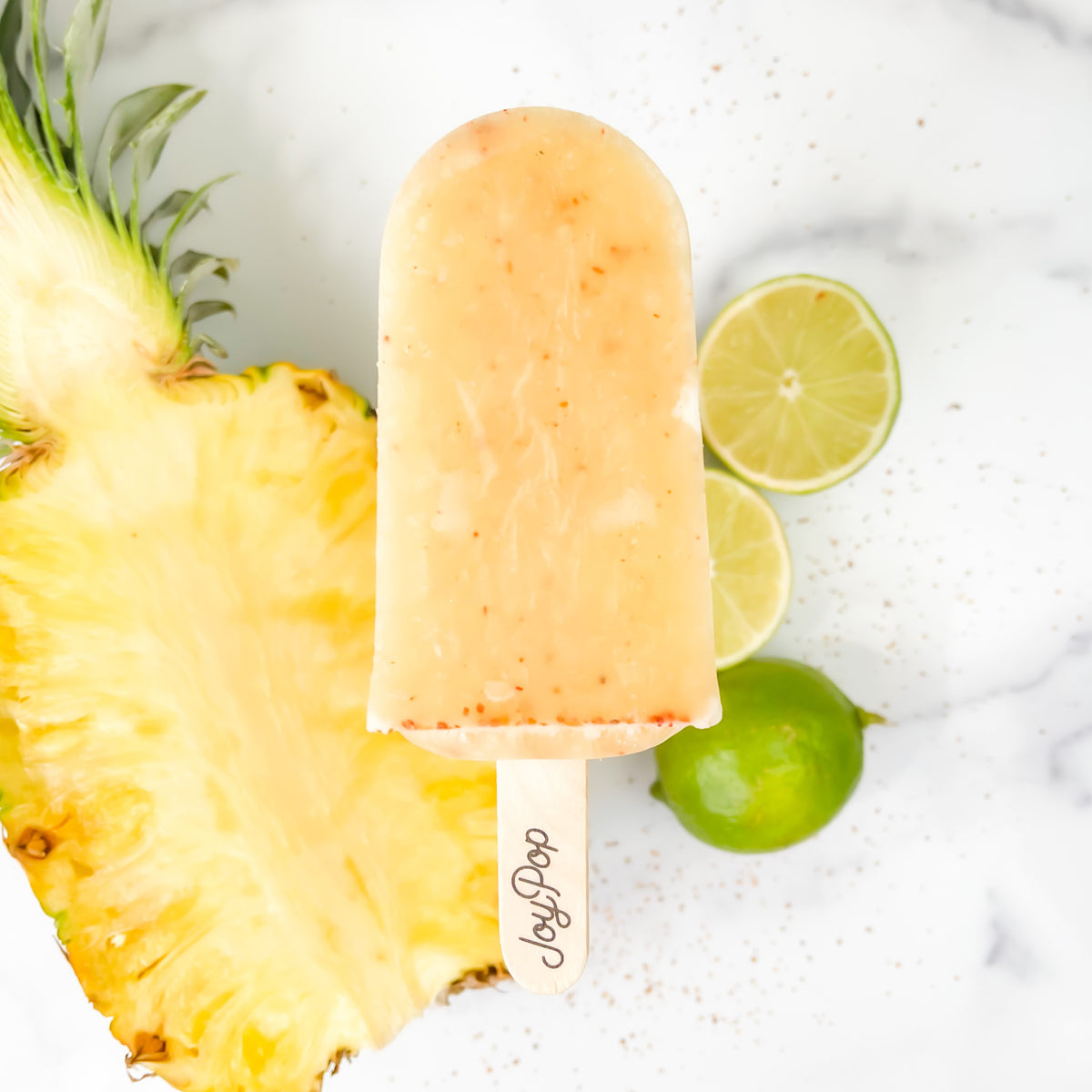 Pineapple Chili Lime Frozen Pop by The Joy Pop Co next to a whole lime and cut limes and a half pineapple and chili spices scattered on a white marble background