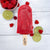 Red raspberry joy pop with a bowl of raspberries and slices of lime on a white wood background