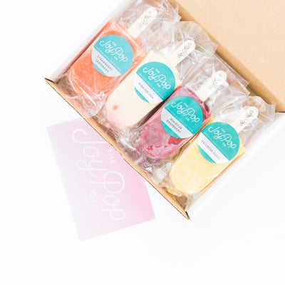 Joy Pop ice pops in hibiscus raspberry wellness blend strawberry lemonade and pina colada in a box with a joy pop card on a white background