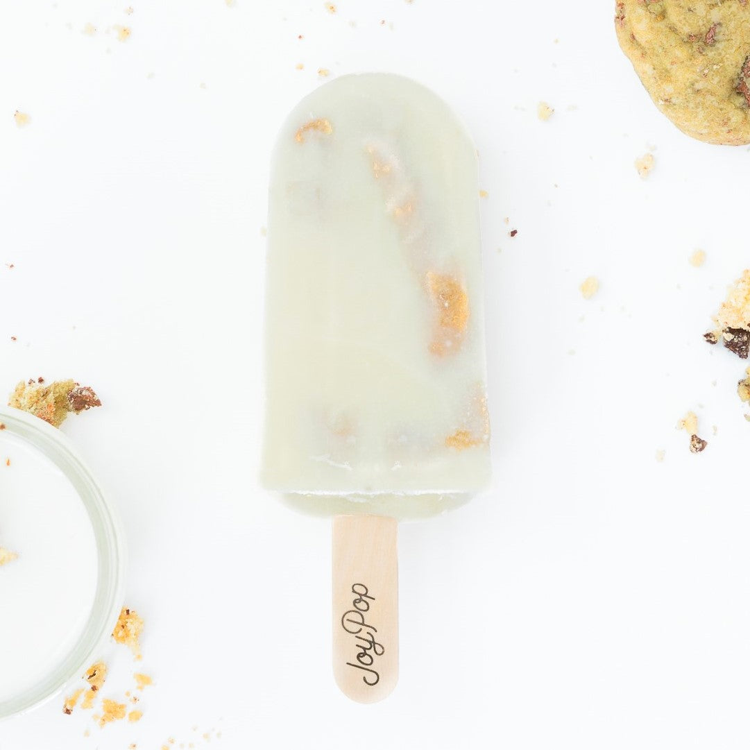 milk and cookies joypop pop with milk and chocolate on the left and two salted chocolate chip cookies on the right on a white background