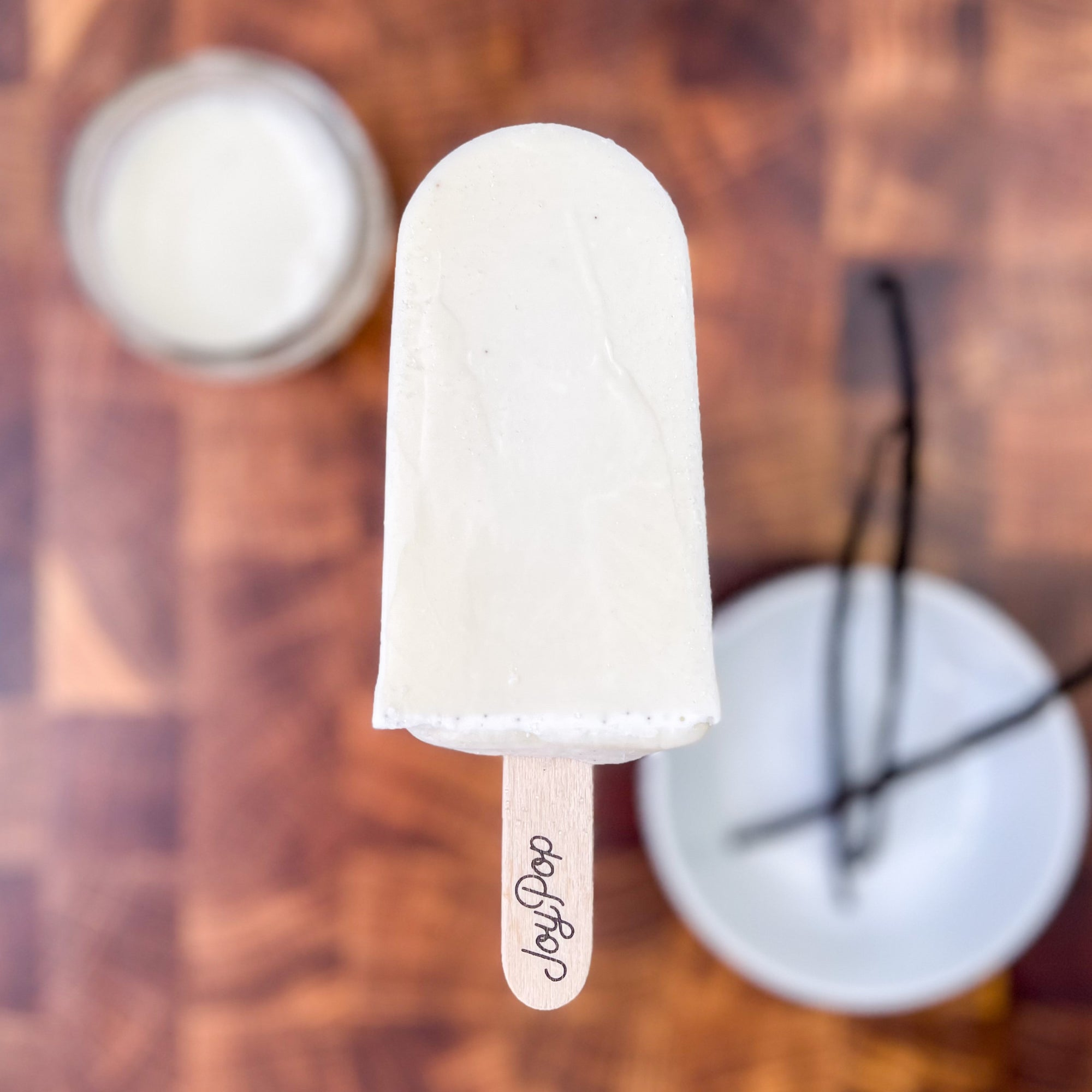 Vanilla Bean pop from The Joy Pop Co with a glass of cream and a bowl of vanilla beans in the background on a dark walnut checkered cutting board
