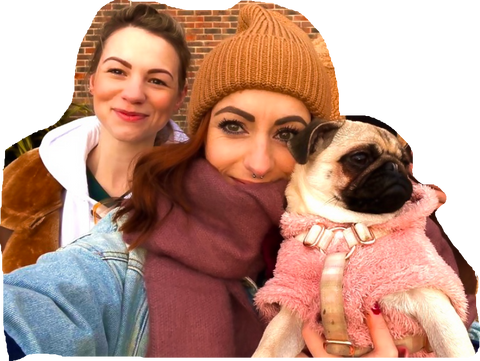 Kirsty & Jasmin (female) wrapped in warm clothing, holding a pug in a pink coat