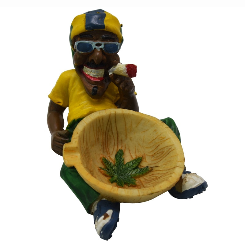 A laughing man wearing sunglasses smoking a joint while holding a basin with a Cannabis Leaf in it. The basin is in between the man's legs and the man is in a laying position propped up on his elbows