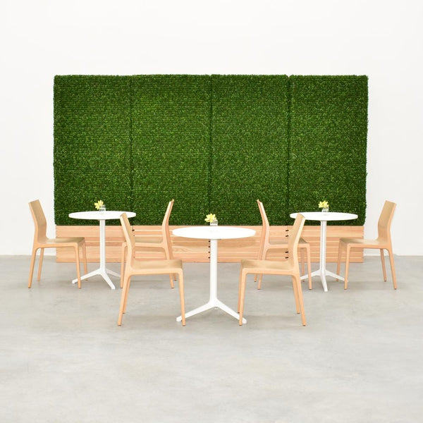 cafe tables with hedge wall backdrop