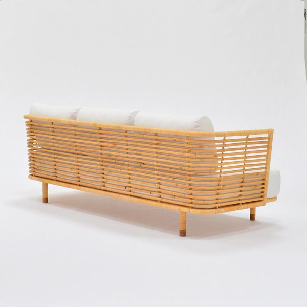 cane sofa natural with white upholstery rear view