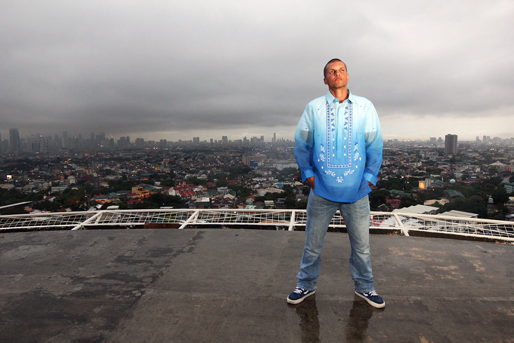 Barong Warehouse's Blue Jusi Monochromatic Barong Tagalog with blue jeans, and sneakers overlooking the Manila skyline.