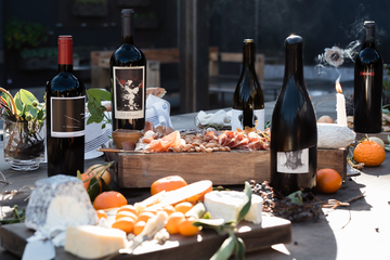 Several bottles of wine on a table with fruit and cheese
