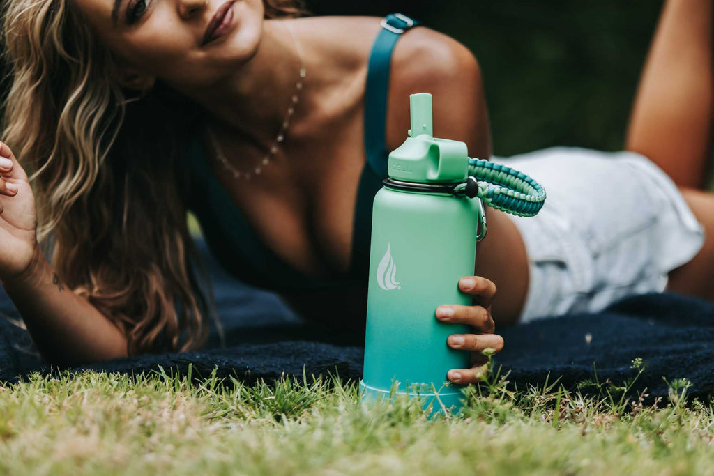 A woman lying on a blanket and holding a water bottle
