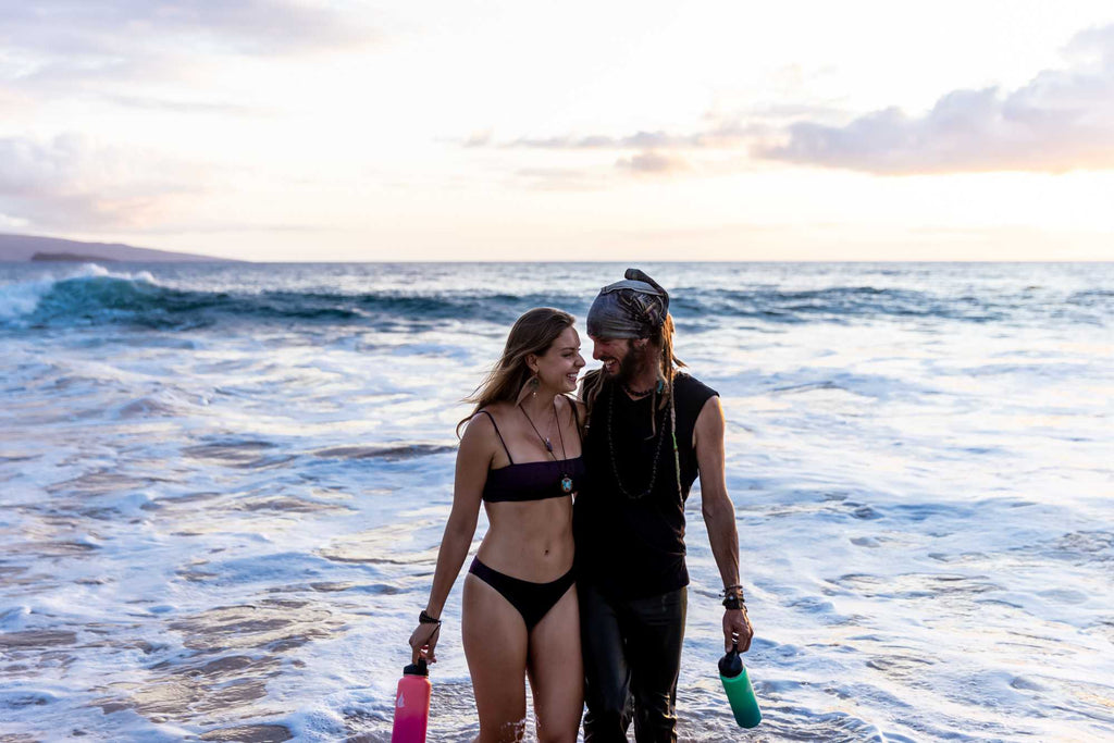 A couple carrying stainless steel water bottles while walking along the beach