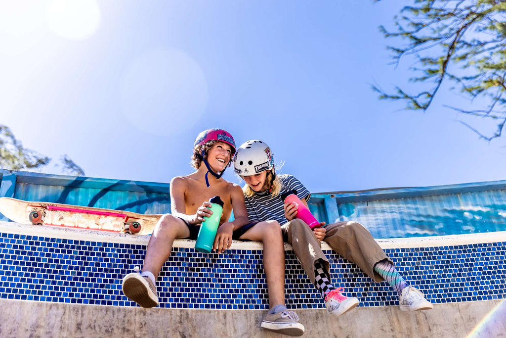 Two kids sitting down while holding stainless steel water bottles