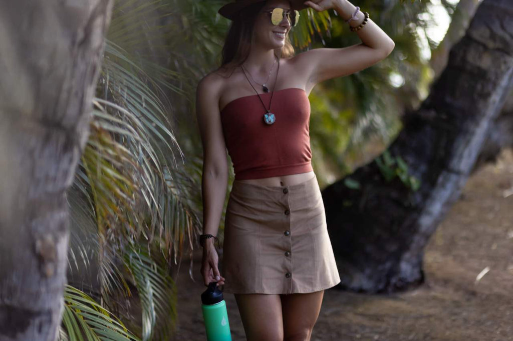 A woman walking along the beach while carrying a water bottle