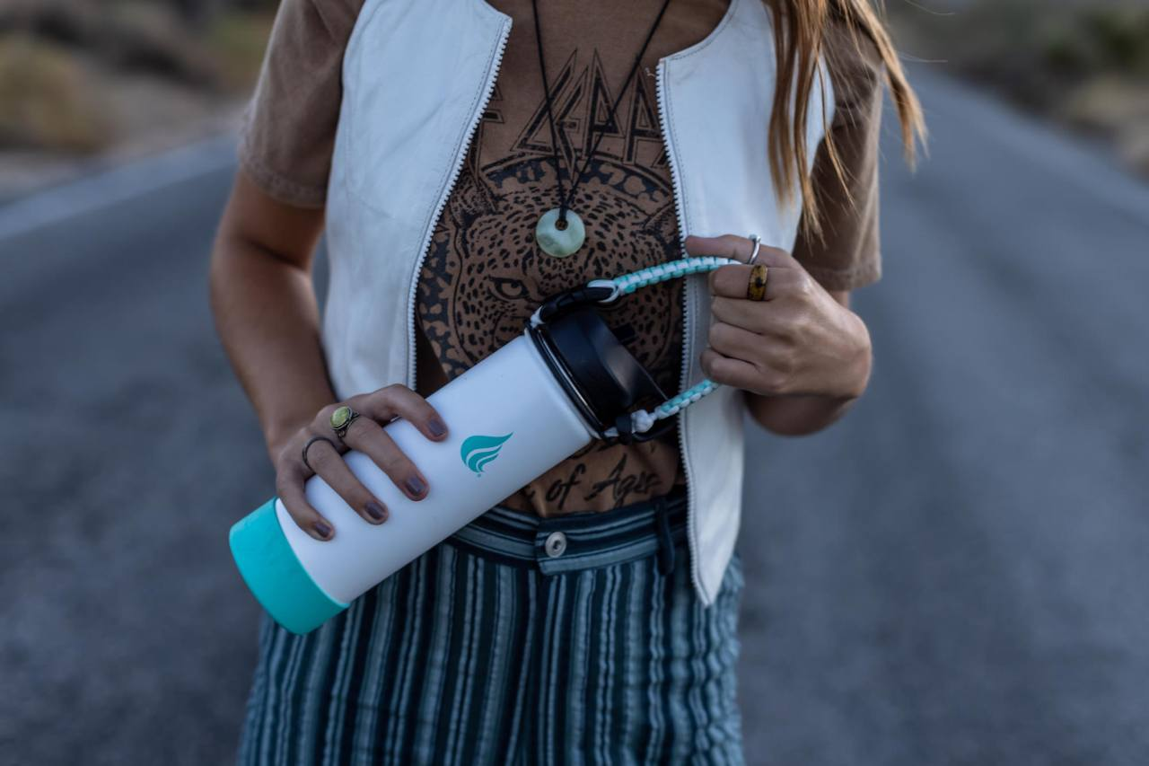 Woman holding a teal and white stainless bottle