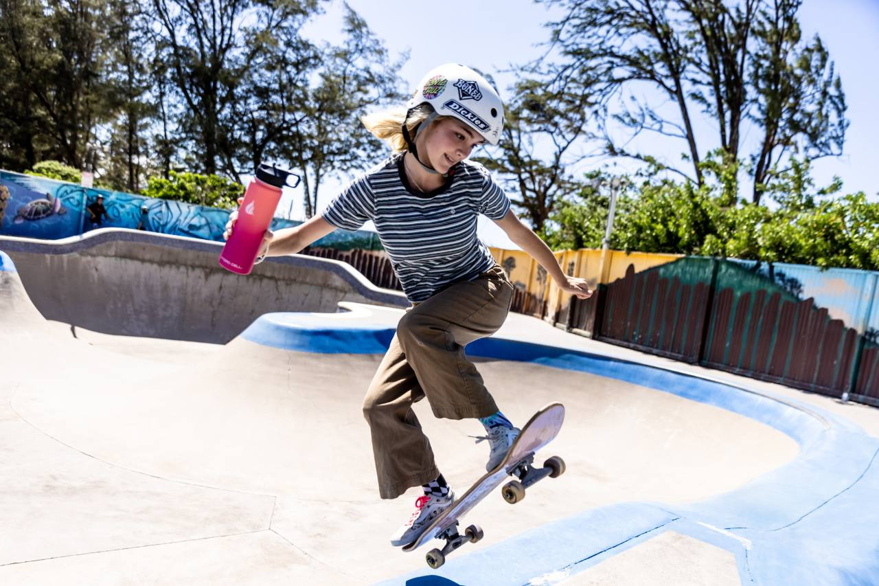 A young girl holding a water bottle while skateboarding