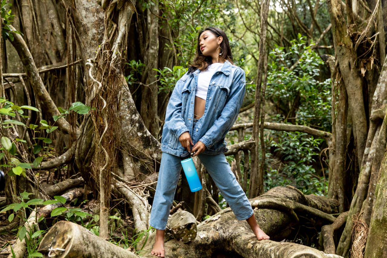A woman standing in the middle of a forest while holding a Hydro Cell water bottle