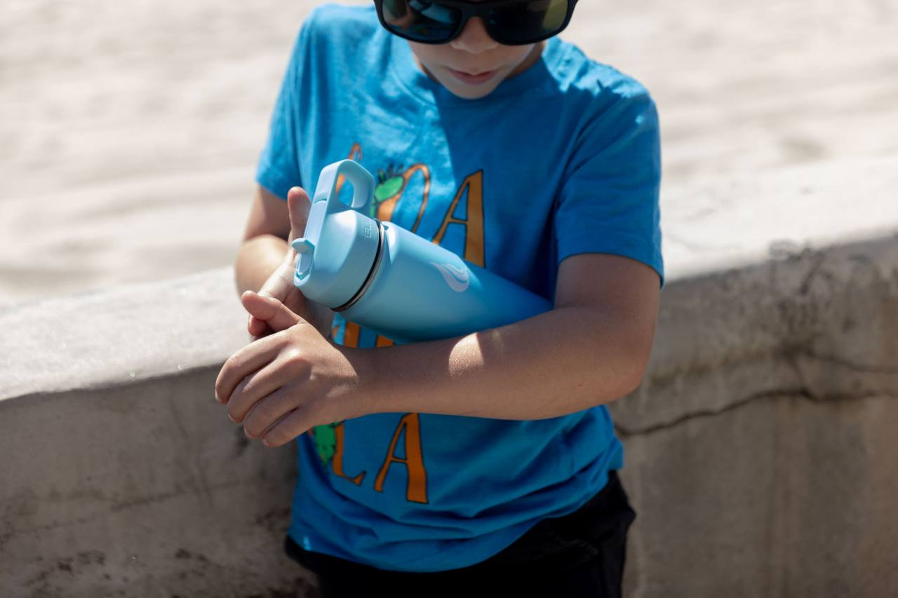A child wearing a blue shirt holding a stainless steel water bottle