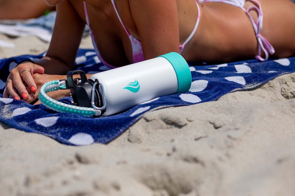 A Hydro Cell water bottle beside a sunbathing woman at the beach
