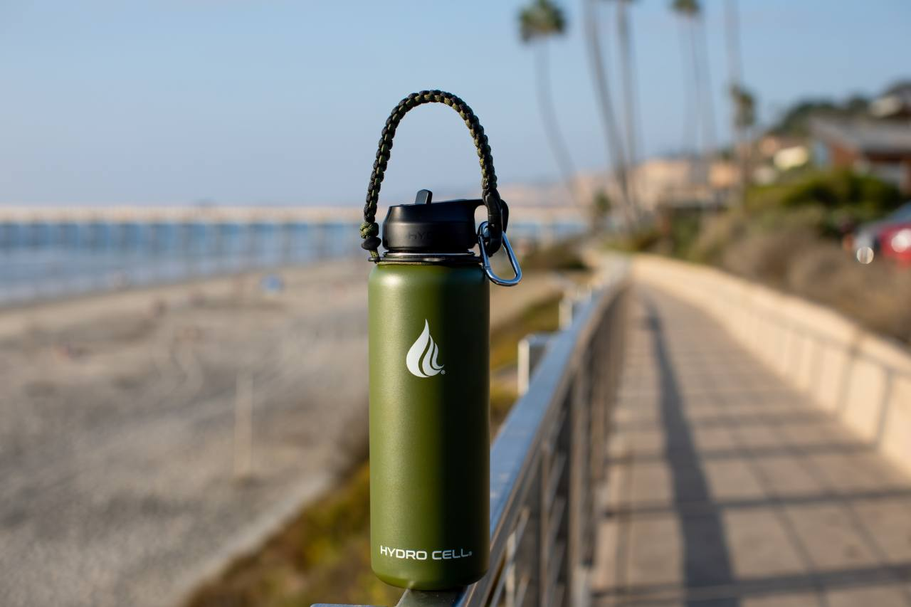 A stainless steel water bottle placed on a railing near the beach