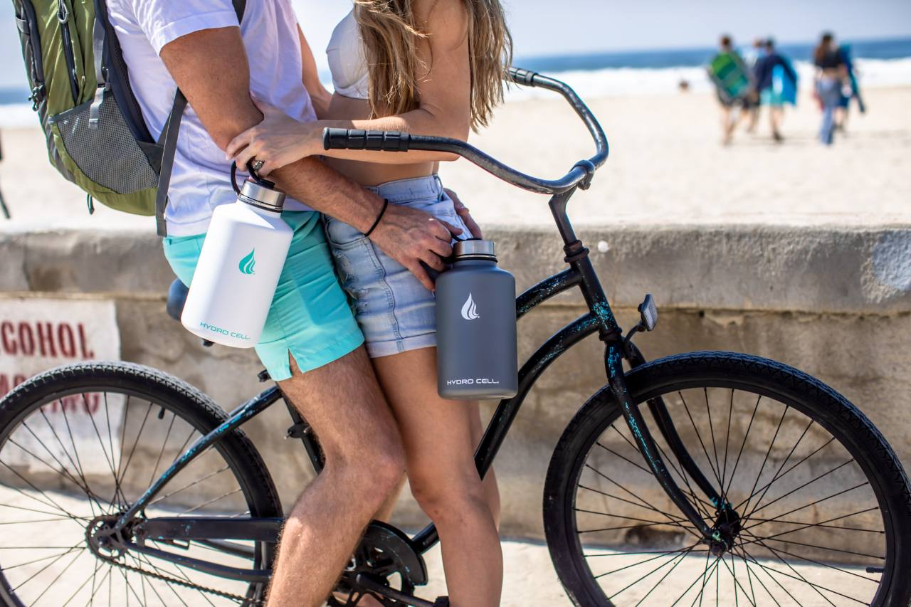 A couple on a bicycle carrying water bottles