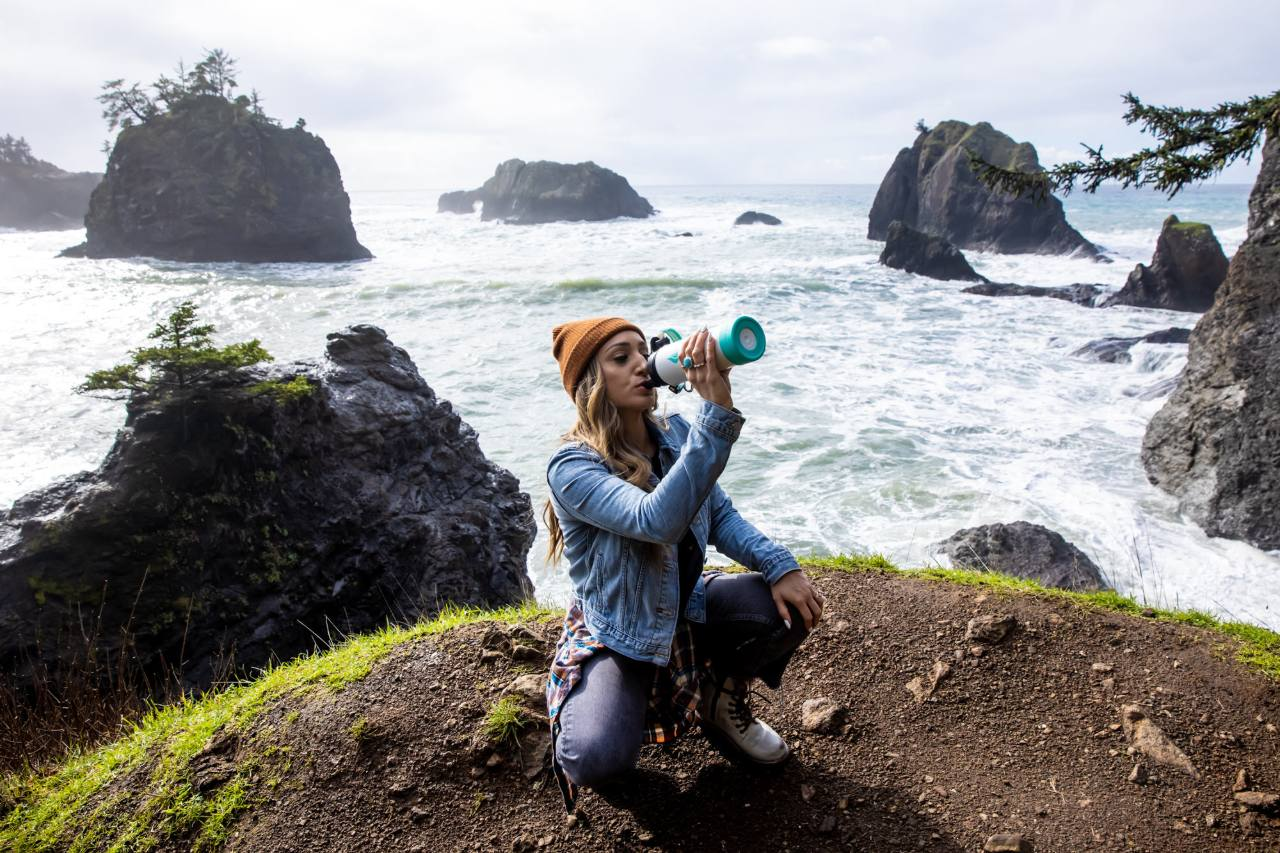 A woman sitting at the edge of a cliff while drinking from a water bottle