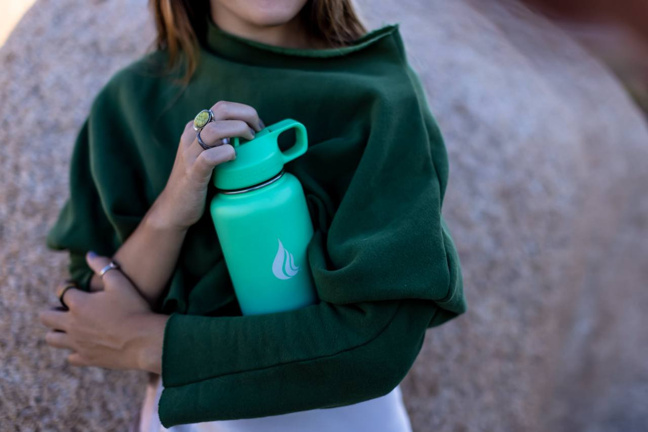 Woman in green shirt hugging a stainless steel water bottle
