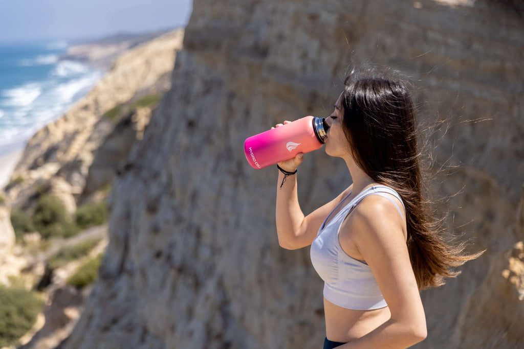 Woman drinking from a pink stainless steel water bottle