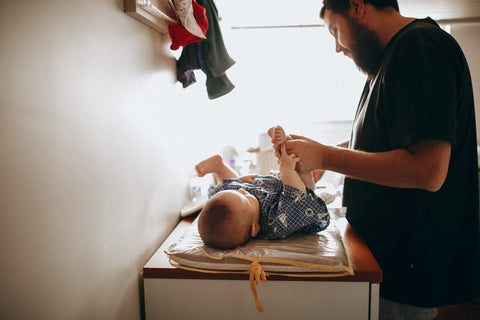 A Dad carefully changes his baby's cloth nappy