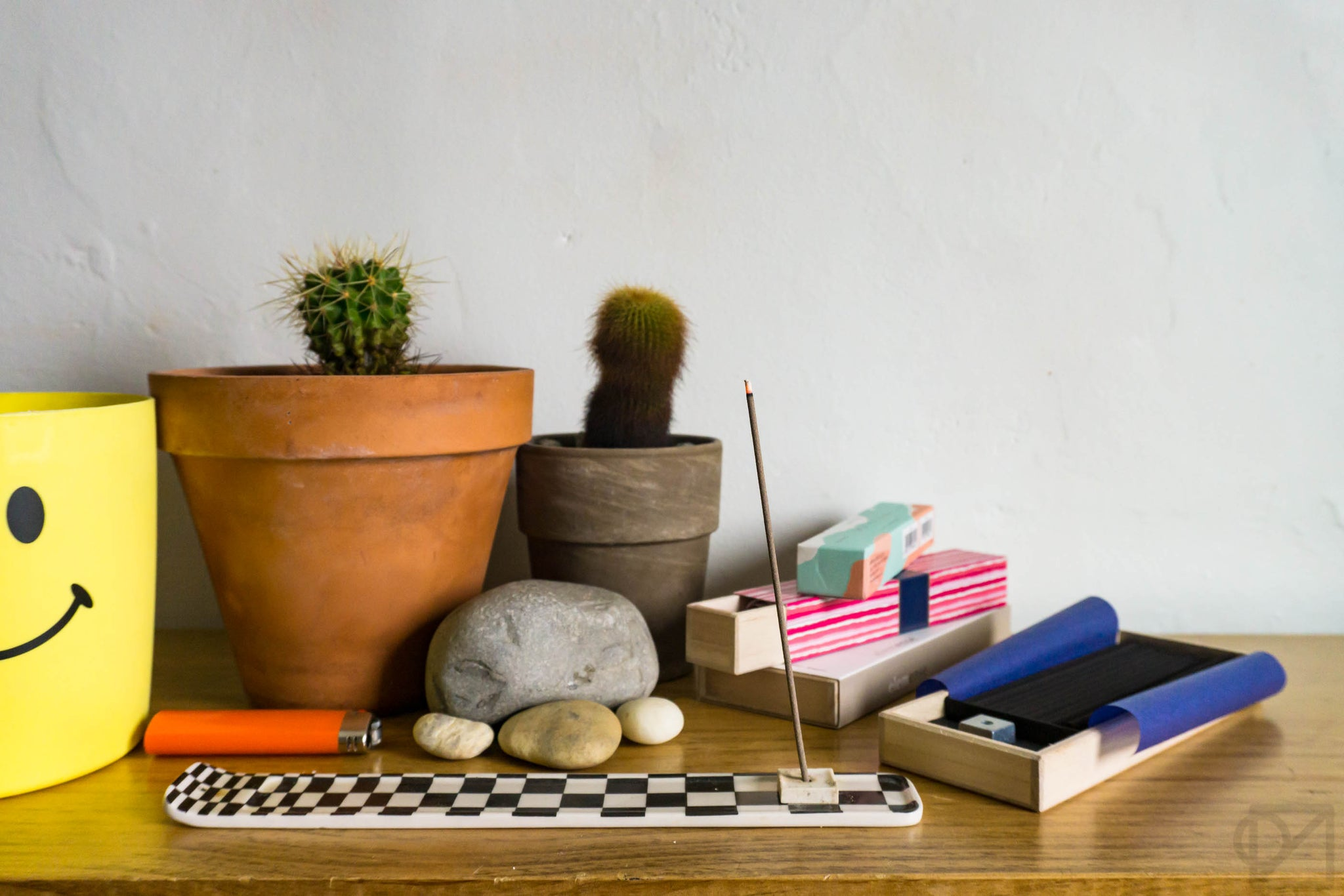 A wooden shelf with 2 small cactus, smooth river rocks, and a stack of different types of incense boxes. One stick is in a checkerboard burner, wafting incense.