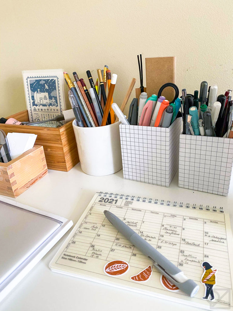 A white desk with a 2021 planner on it. There are square pen holders full of pens along the edge of the desk.