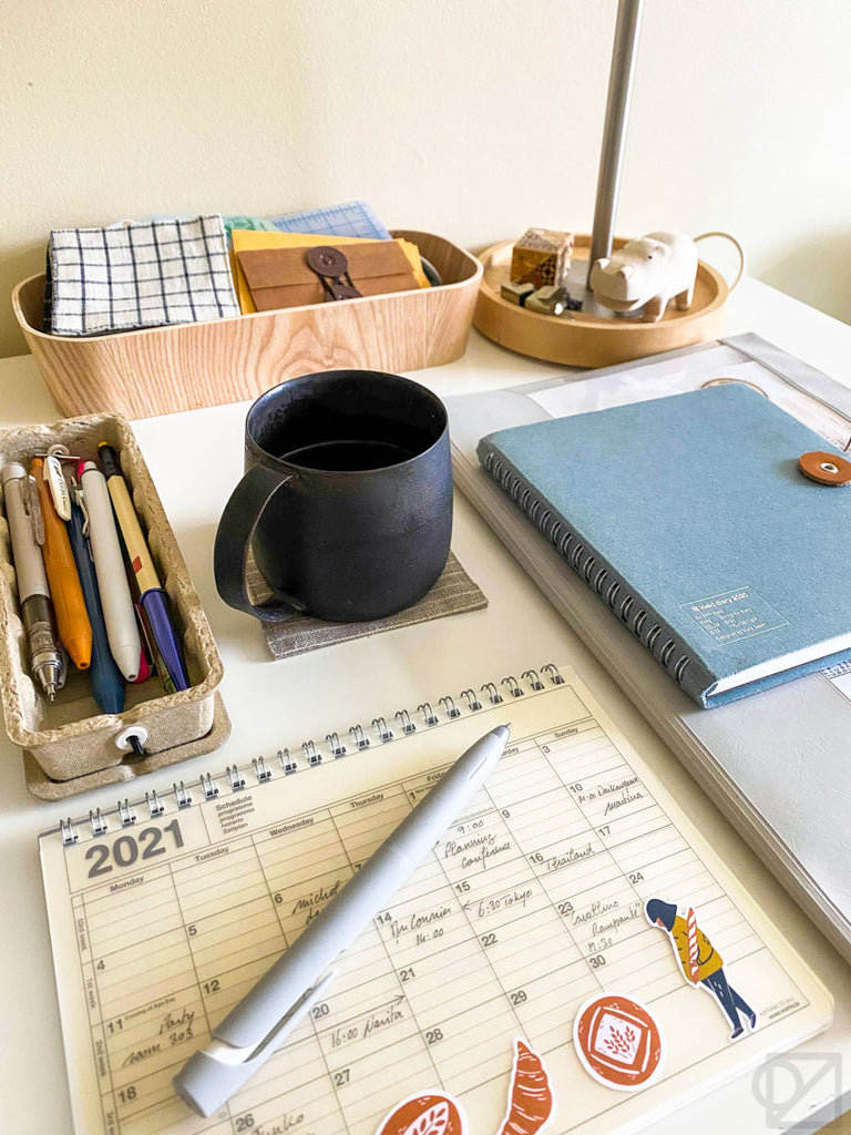 The desk with a pencil case, coffee mug, and a few books, neatly arranged in a grid.
