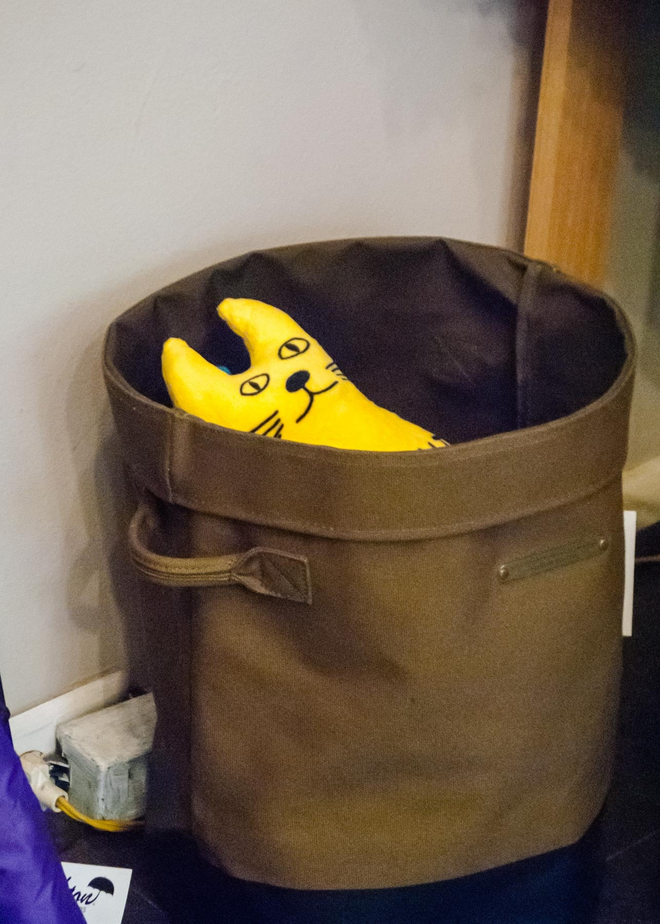 A sketchy looking yellow plushie cat stares out from a canvas storage bin.