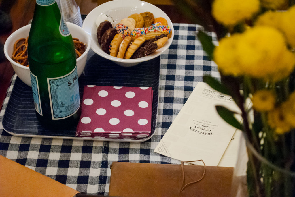 cookies, pretzels, and sparkling water for guests, sitting on a gingham tablecloth