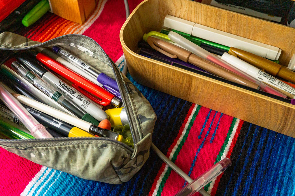 A cloth pencil case and a wood tray both full of pens and pencils on a colorful Mexican tablecloth.